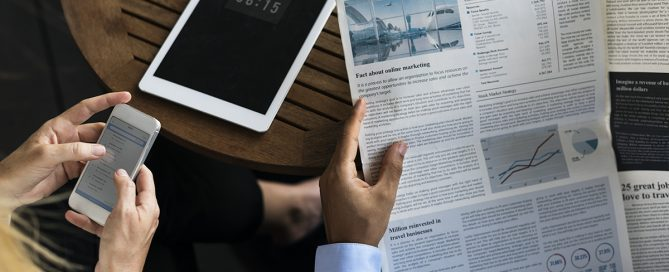 person holding newspaper and tablet on table